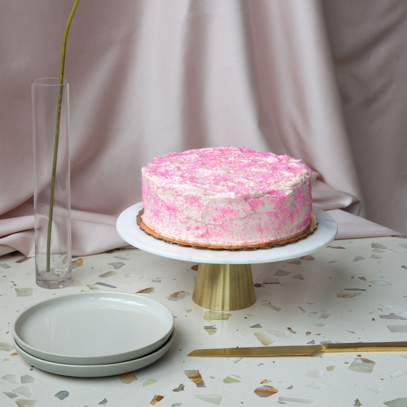 Pink cake on a marble and brass wedding cake stand