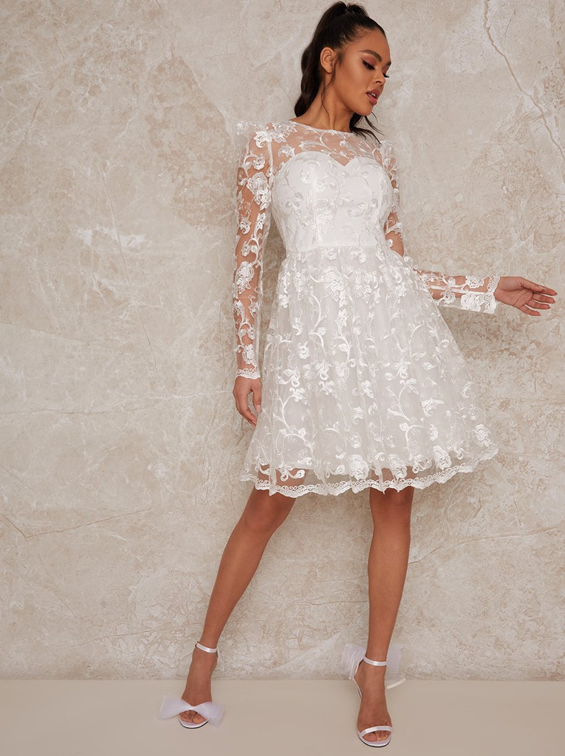 Model wearing a short dress with long lace sleeves