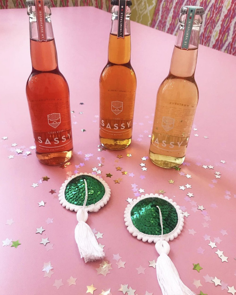 Three bottles of peach and gold coloured cider on a pink tablecloth covered in sequin stars next to green and white sequinned DIY nipple tassels