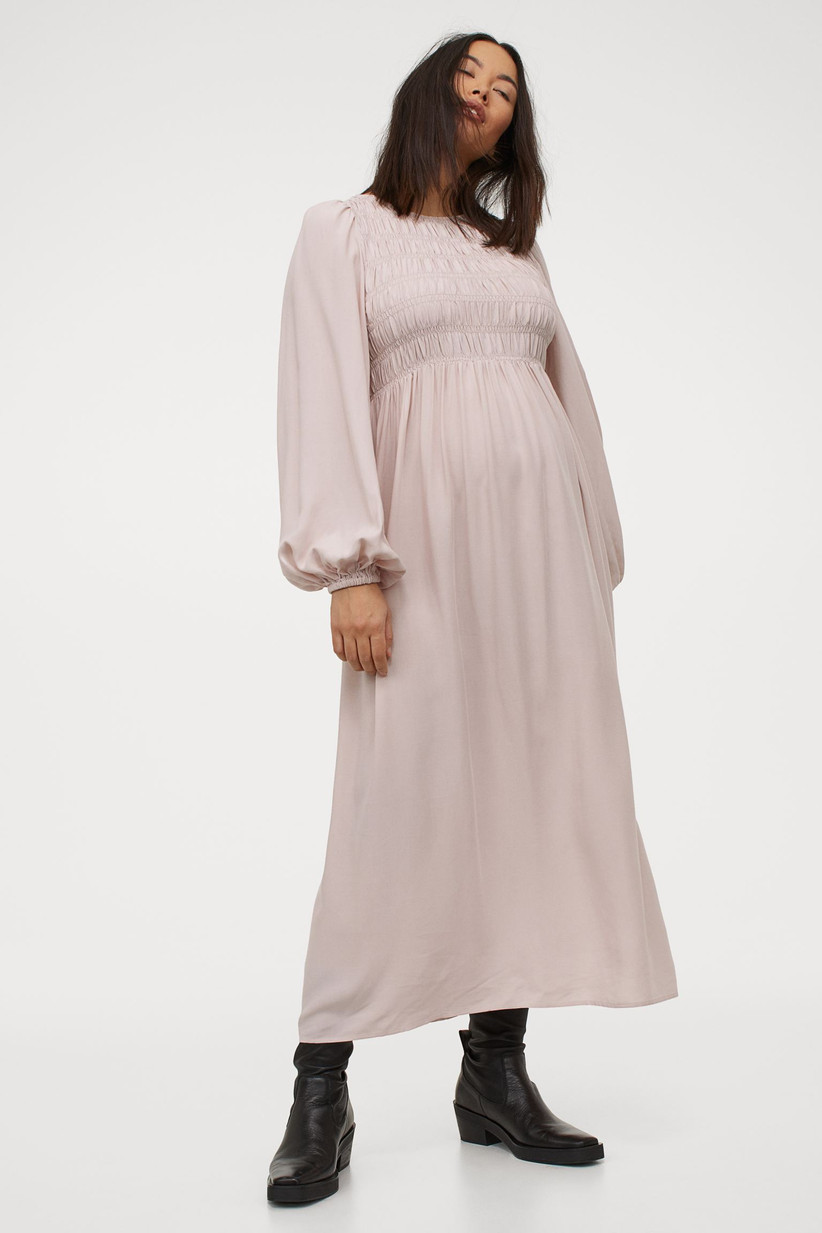 Model wearing pink maxi maternity dress with smocked bodice and long sleeves