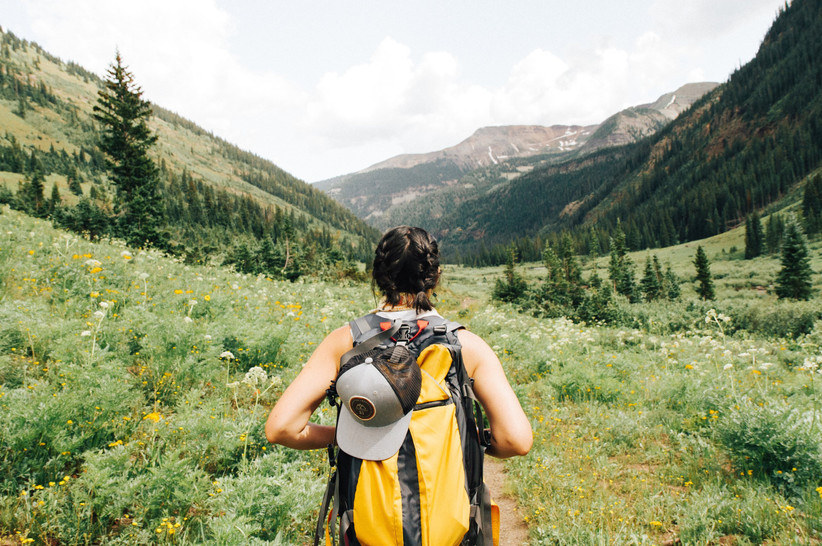 White woman with short dark hair in French plaits with a yellow backpack hiking through a green valley