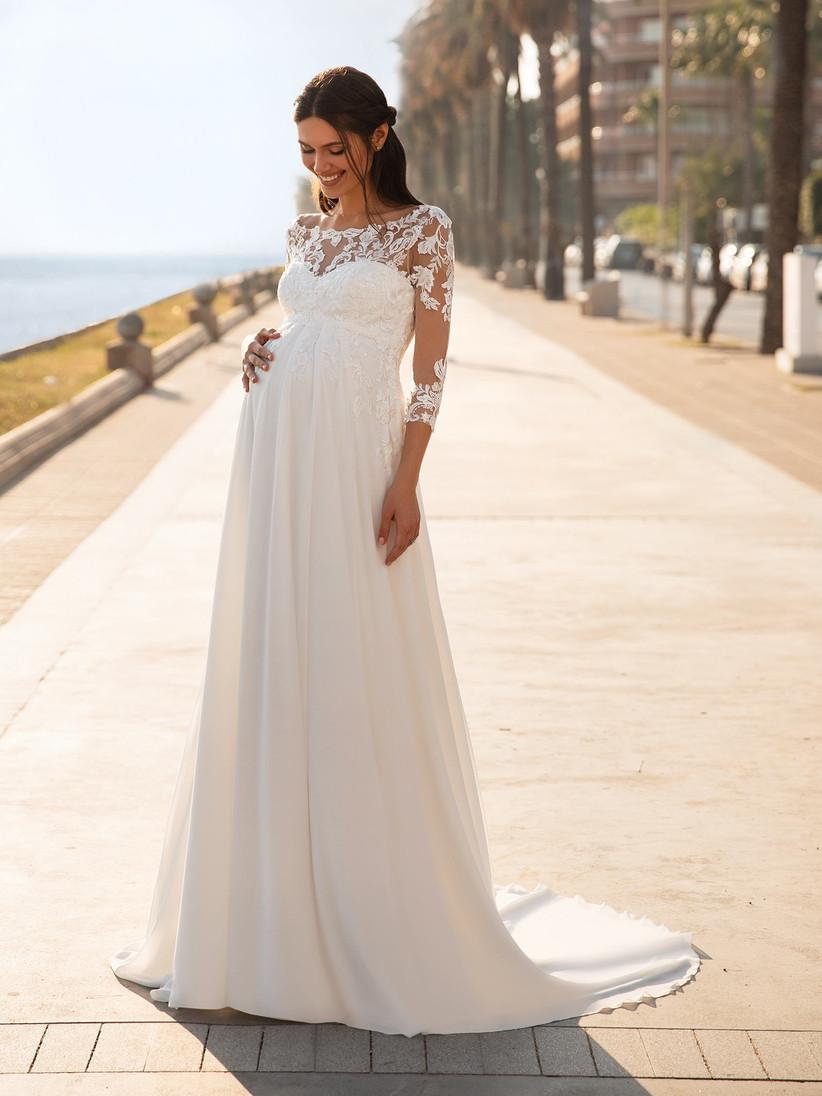 Model wearing white lace long sleeve maternity wedding dress