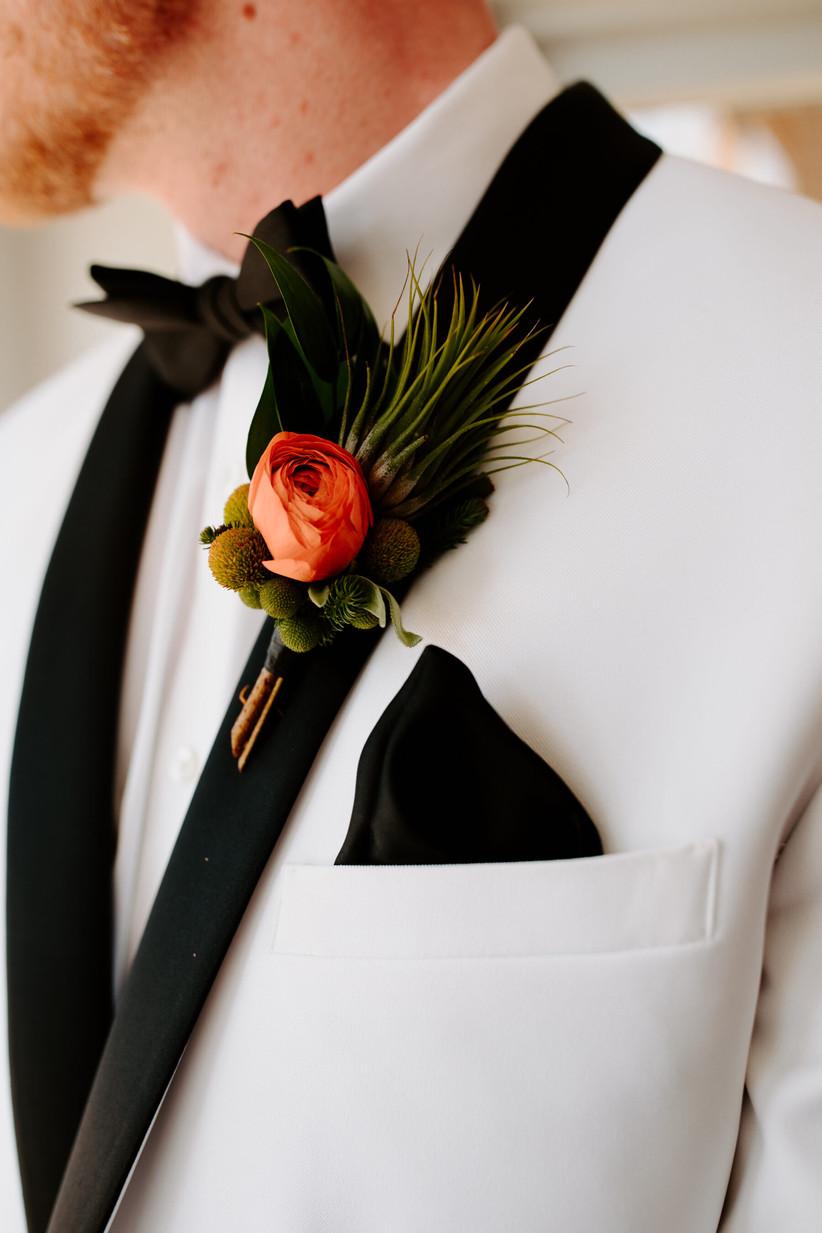 Groom wearing an orange floral wedding buttonhole