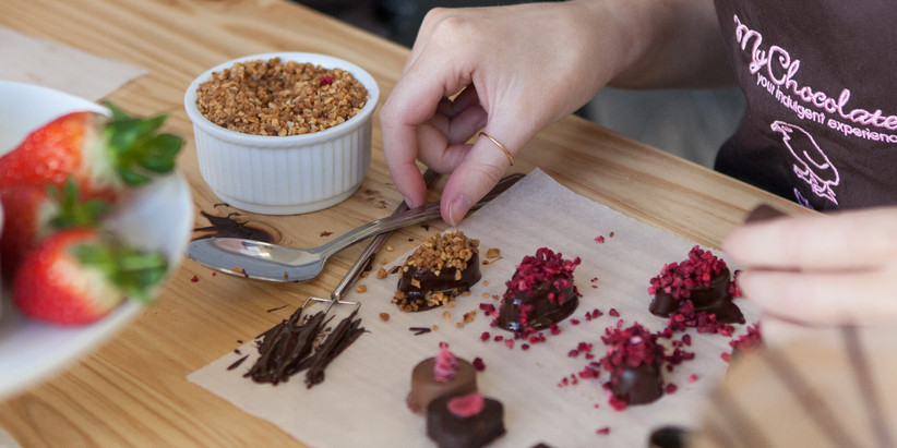 White woman in brown and pink apron making nut and berry scattered dark chocolate truffles on a wooden table