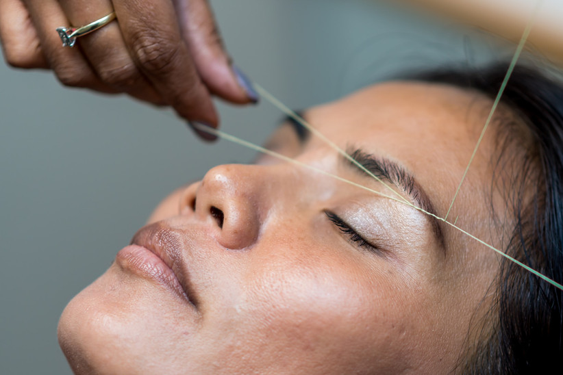 Women with her eyes closed having her eyebrows threaded