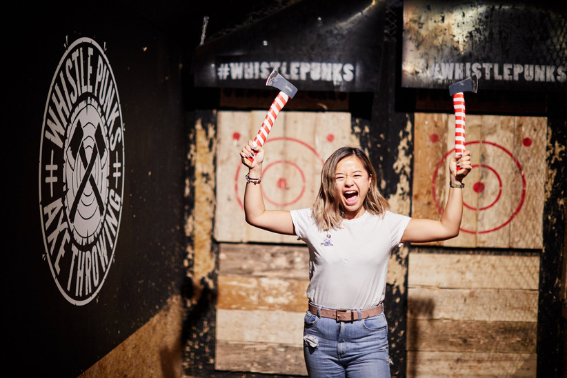 Smiling Asian woman in a white t-shirt and jeans holding two axes aloft with wooden targets behind her