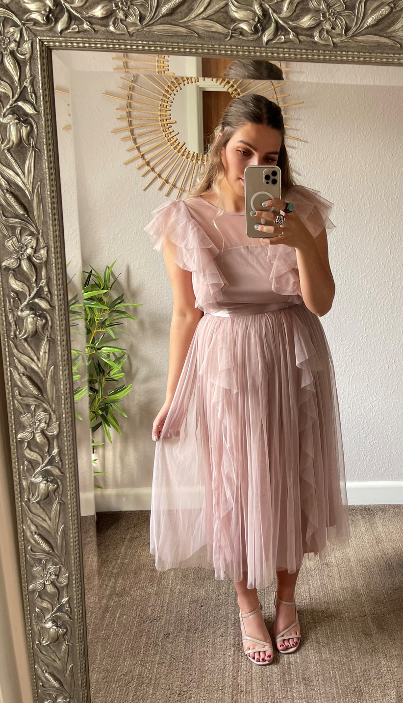 Model wearing pink ruffle bridesmaid dress
