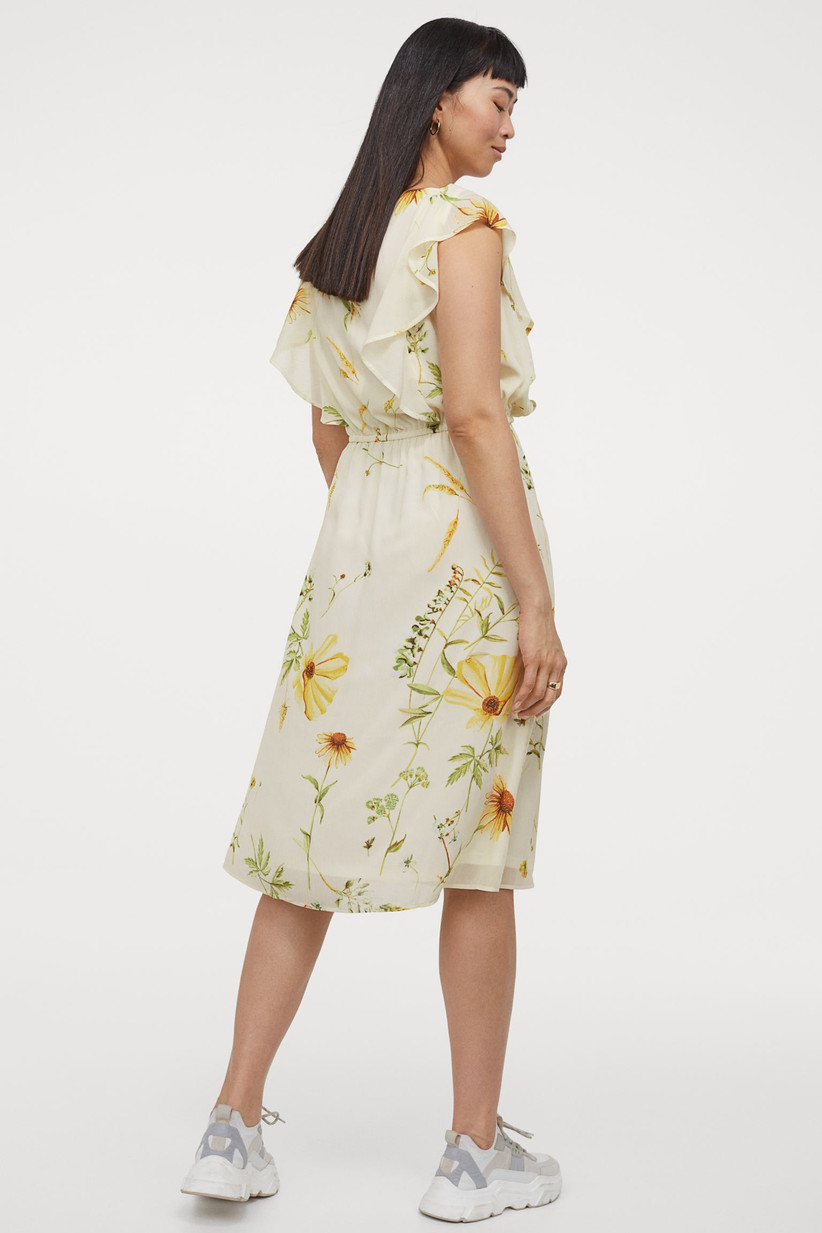 Model wearing a white and yellow floral midi dress