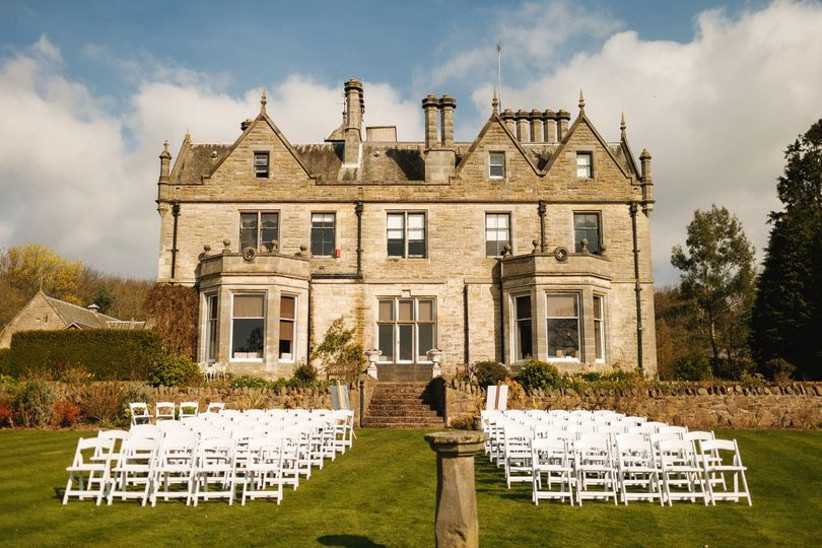 Outside wedding ceremony area with white chairs
