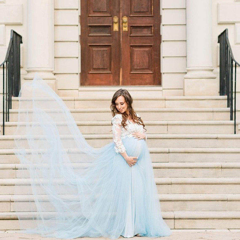 Model wearing maternity dress with a white long sleeve top and a pale blue tulle skirt