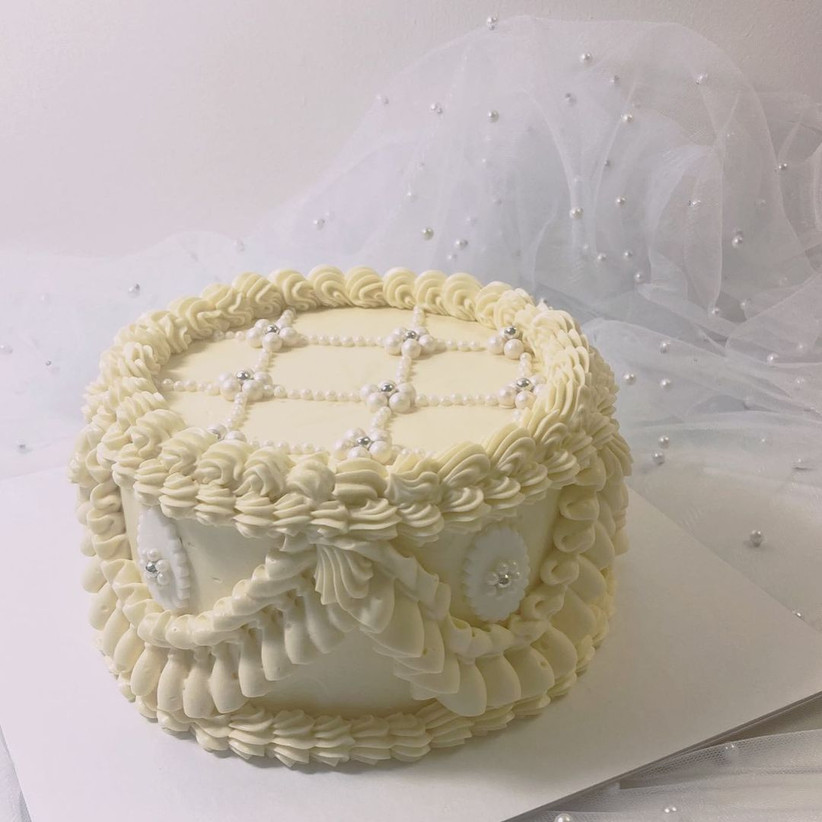 White ruffled cake with peals