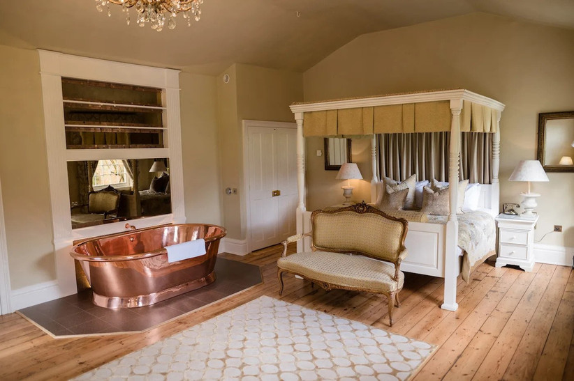 Bridal suite bedroom at Fennes with bed and freestanding copper bath