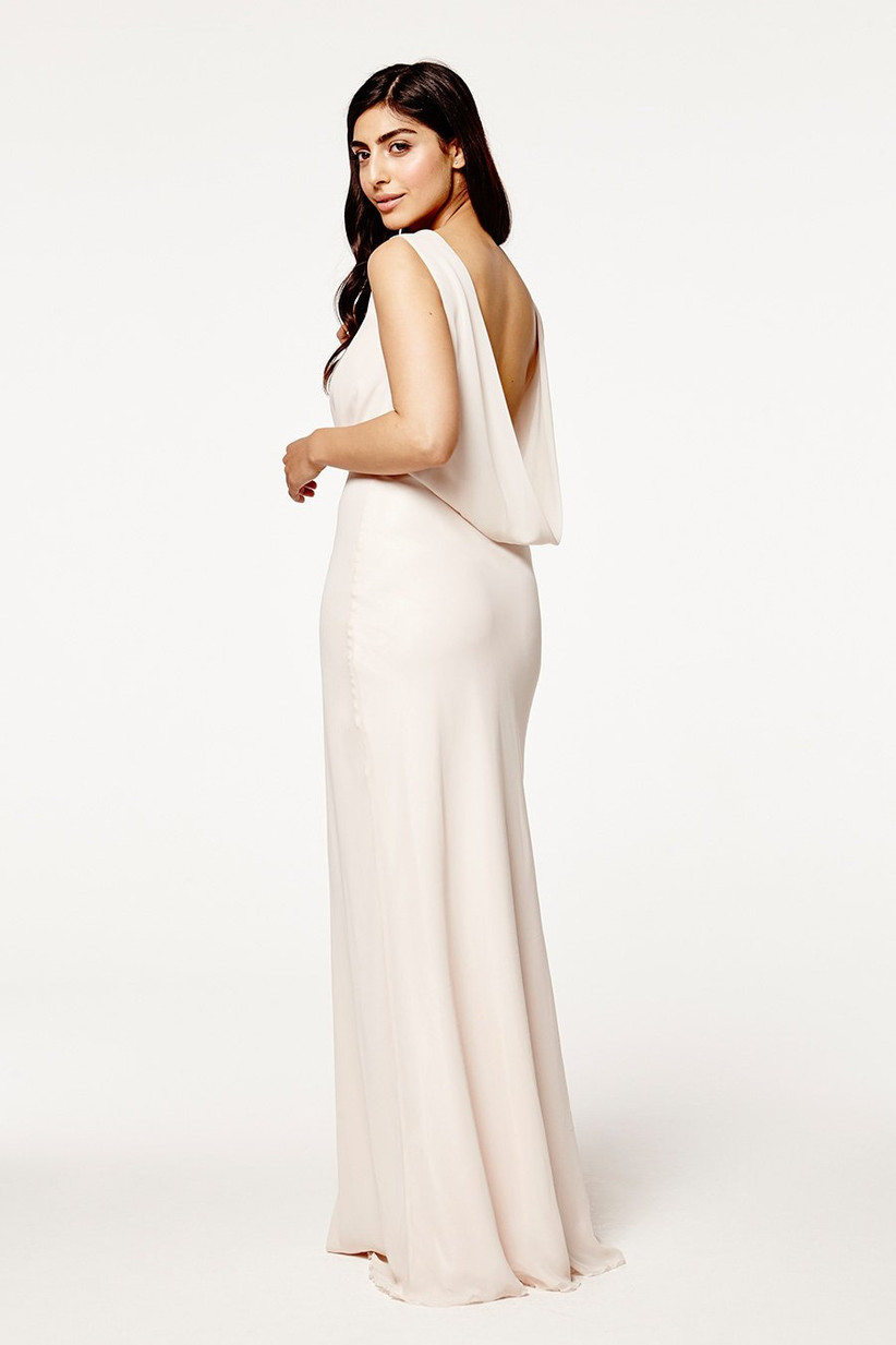 Model wearing a low back white bridesmaid dress
