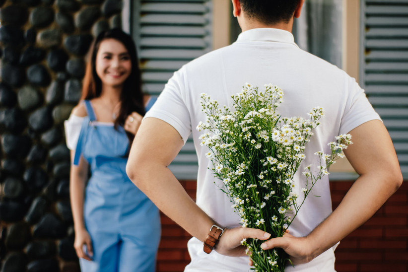 man suprising woman with flowers