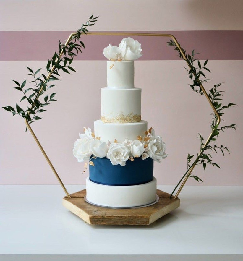 Hexagon wedding cake stand with a white and navy cake