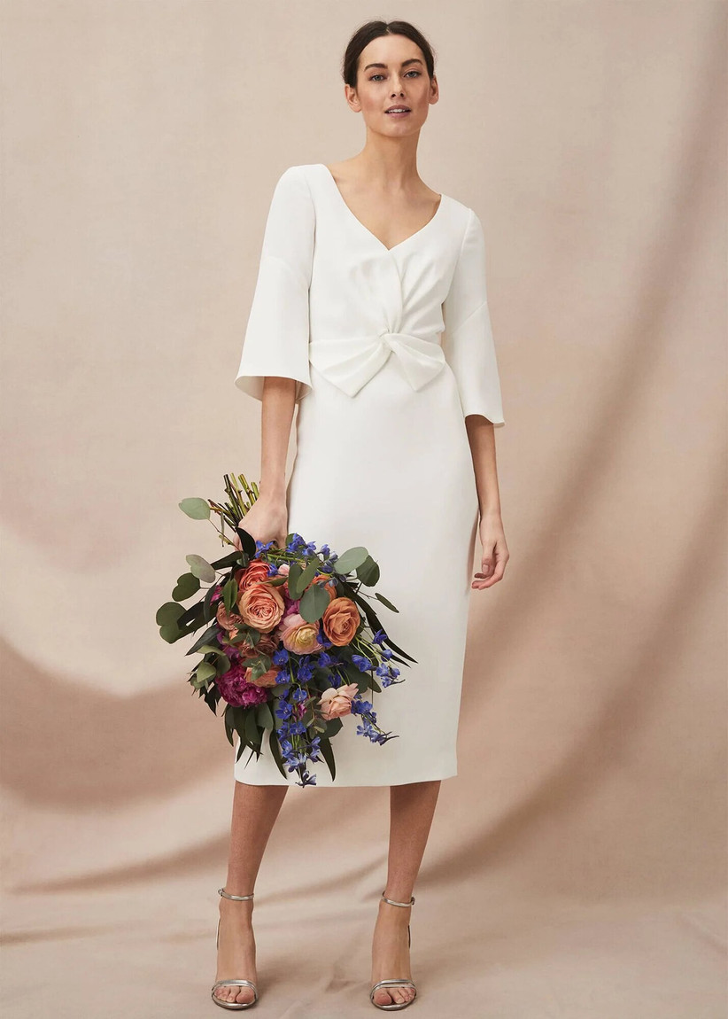 Model in a long sleeved wedding dress with a bright bunch of flowers