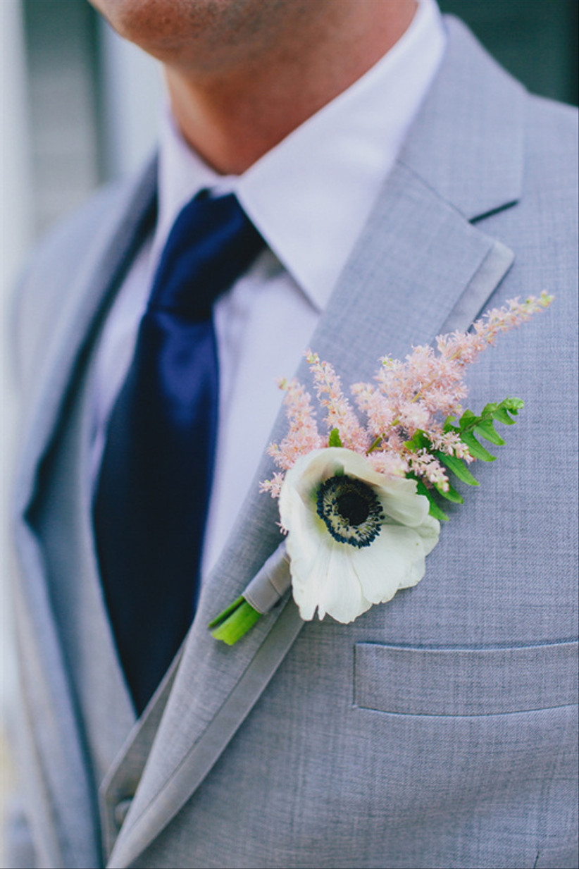 Groom wearing a white poppy wedding buttonhole