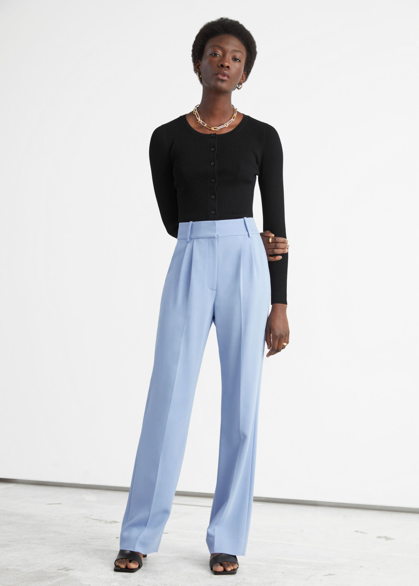 Model wearing pale blue trousers with a long-sleeve black top