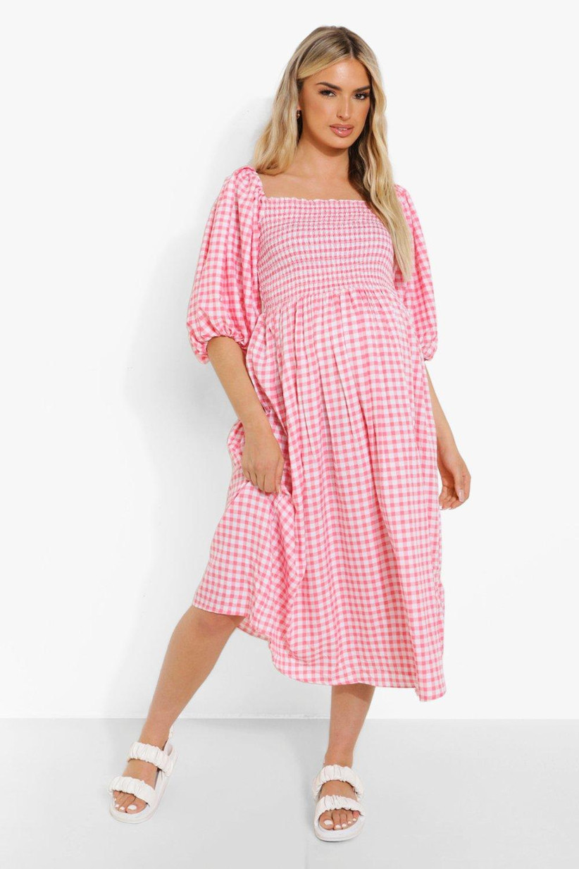 Pregnant model wearing a gingham pink wedding guest dress