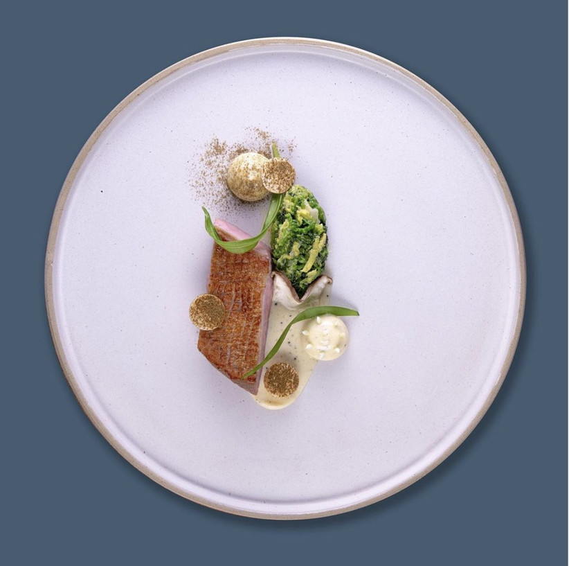 White plate on a blue tablecloth with a fried fillet of fish, potato and greens
