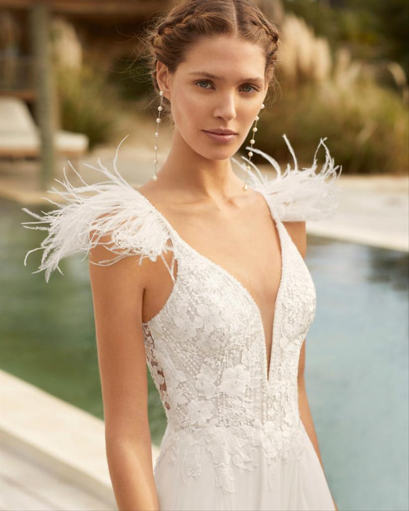 Model wearing a feather shoulder wedding dress