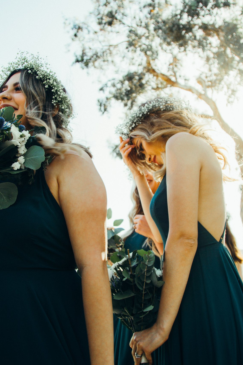 Two bridesmaids wearing green dresses