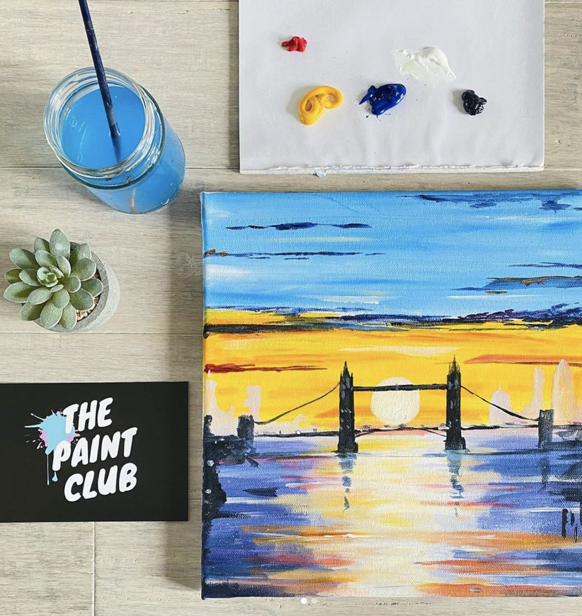 Canvas painting of London Bridge on a wooden table with a paintbrush and pot and a succulent