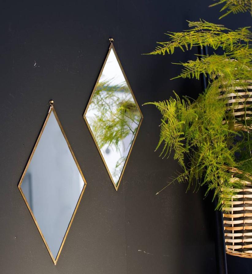 Diamond shaped mirror hanging on a black wall