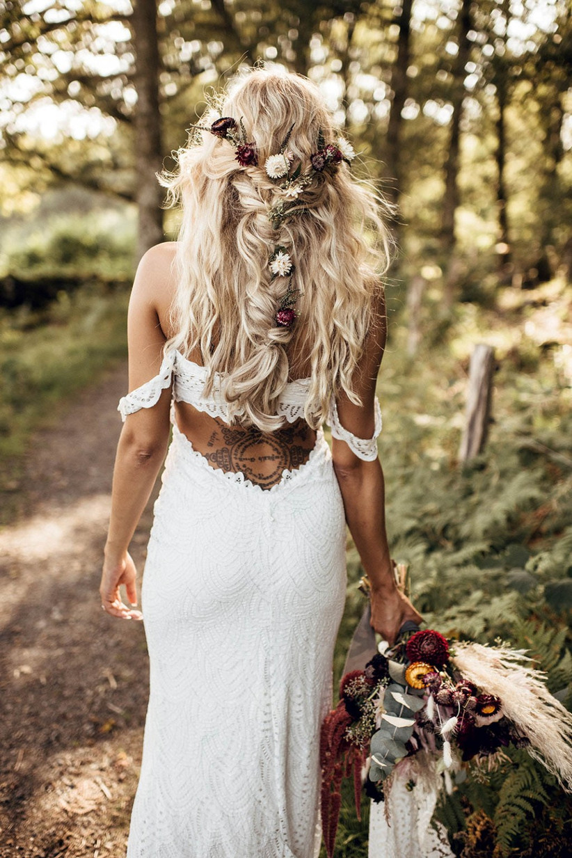 Model with a flower adorned plait and beachy waves