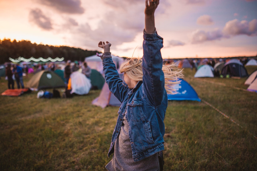 Blonde woman in a denim jacket dancing in the sun in a field full of coloured tents