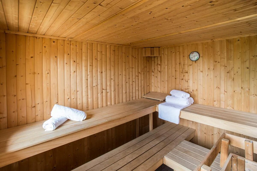 Wooden sauna with white towels