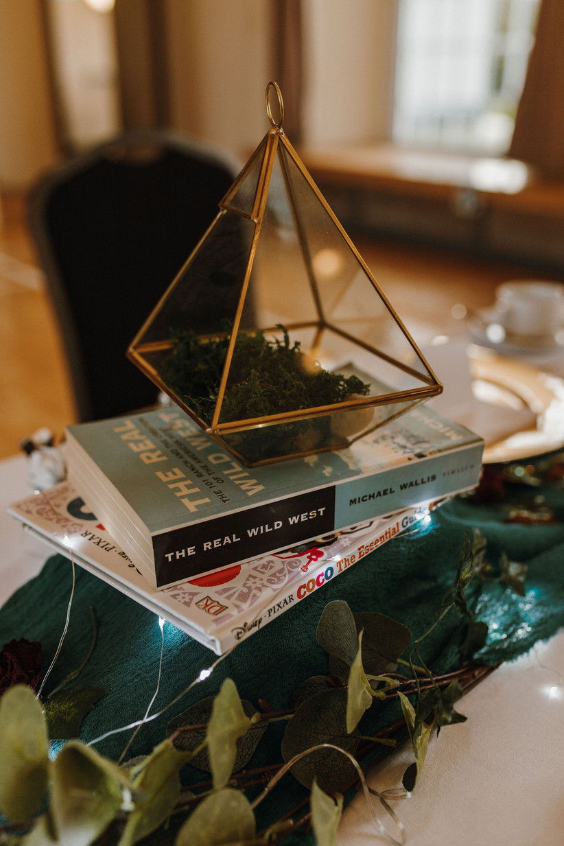 A geometric candle holder filled with greenery on a table at the reception