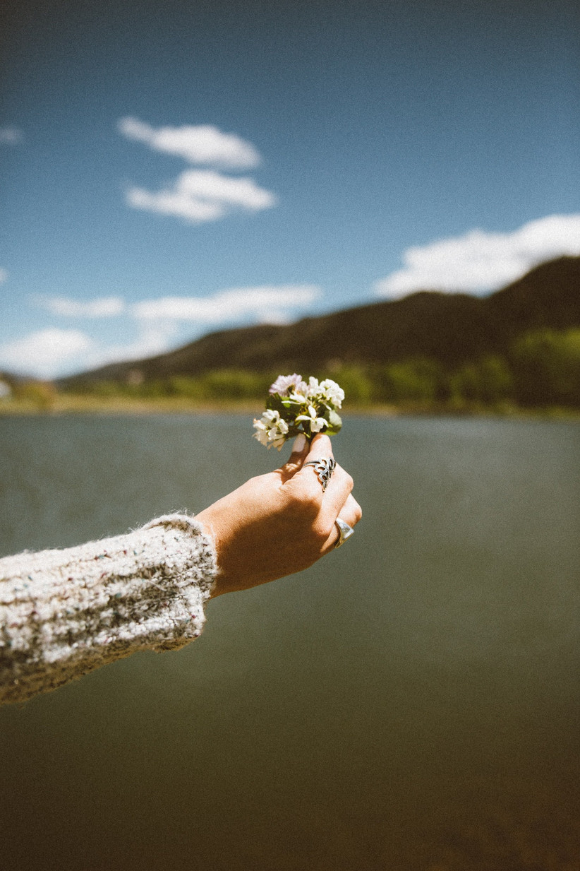 Woman wearing a cream woollen jumper next to a lake and mountain wearing an ornate silver ring and holding out a bunch of small white flowers