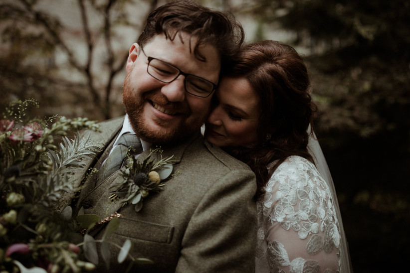 Laughing white groom with a beard and glasses wearing a light green tweed suit with a thistle buttonhole holding a foliage bouquet with his bride leaning on his shoulder wearing an embroidered floral white wedding dress