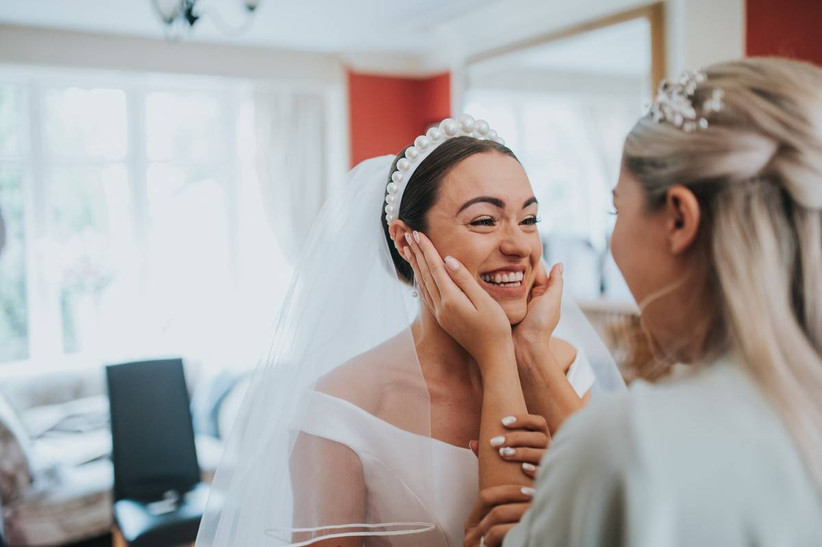Bridesmaid holds the face of a smiling bride