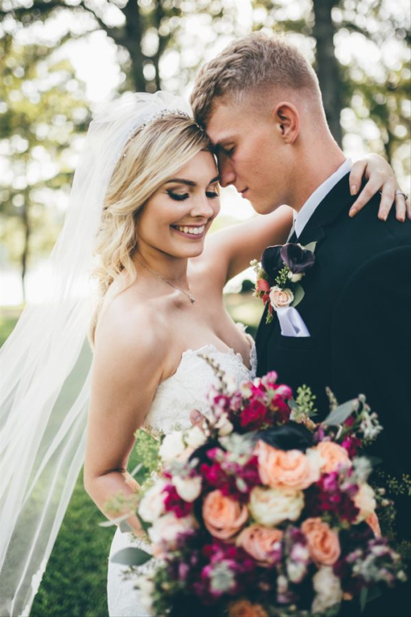 Bride with long veil standing with a groom holding a bouquet