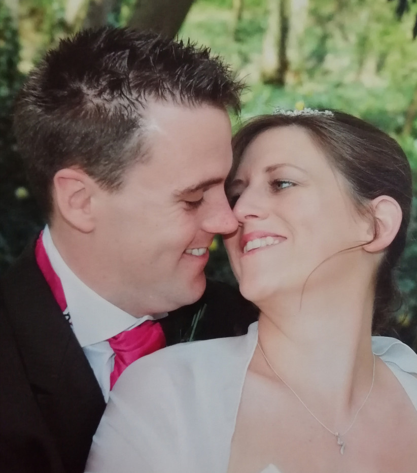 Closeup of white bride with brunette hair tied back smiling and about to kiss her white husband with dark hair and bright pink tie