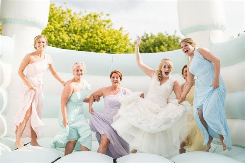 bridesmaids-in-pastel-dresses-on-a-bouncy-castle