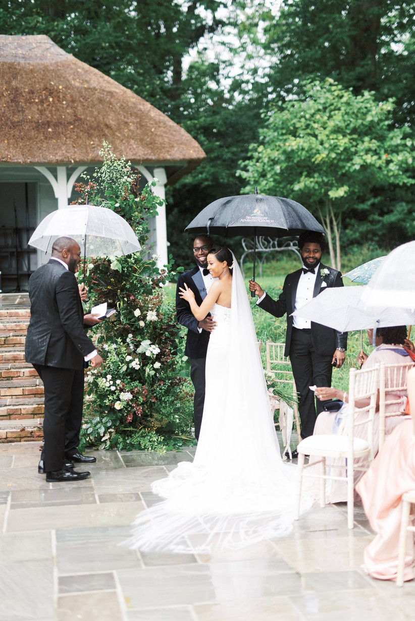 Bride and groom getting married under an umbrella