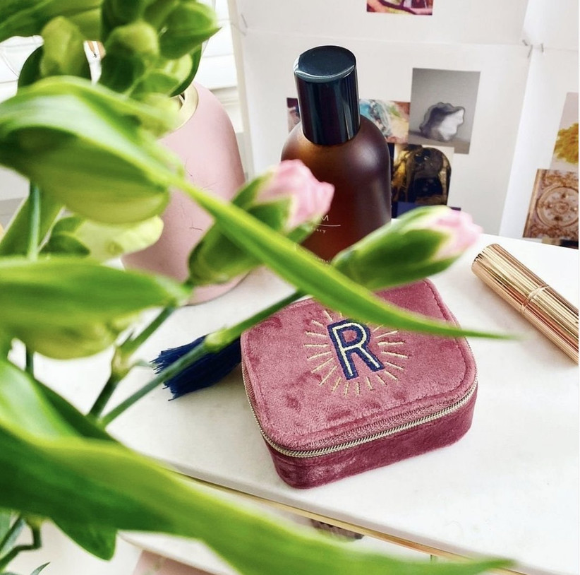 Bright pink velvet travel jewellery box with a blue and gold monogram letter and blue tassel on a dressing table