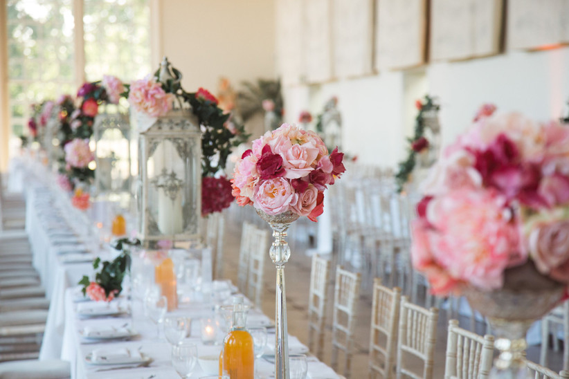 Long wedding tables decorated with tall arrangements of pink flowers