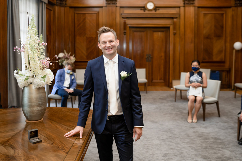 Groom waiting for bride in ceremony room as masked wedding guests look on