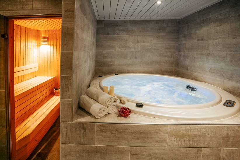 Hot tub with rolled up towels next to a sauna