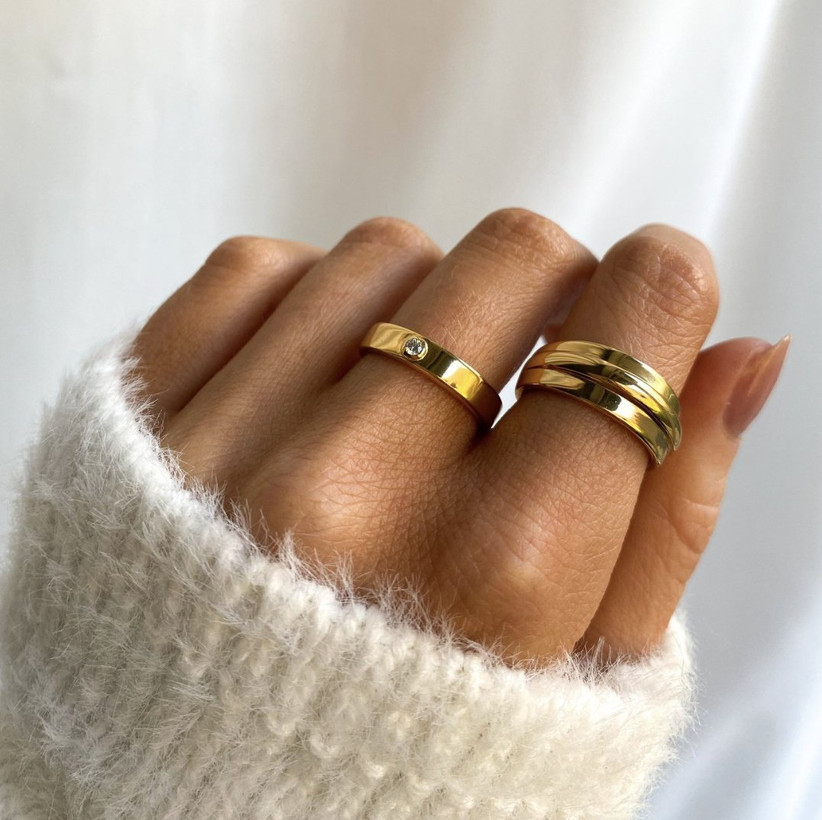 Close up of woman's hand wearing a central gold ring with a diamond in the middle and a layered gold ring on her first finger