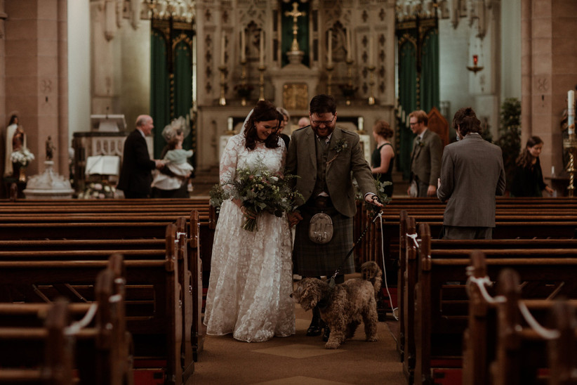 White bride and groom walking back down the aisle of a church with their dog on a lead in front of them and wedding guests in pews behind them