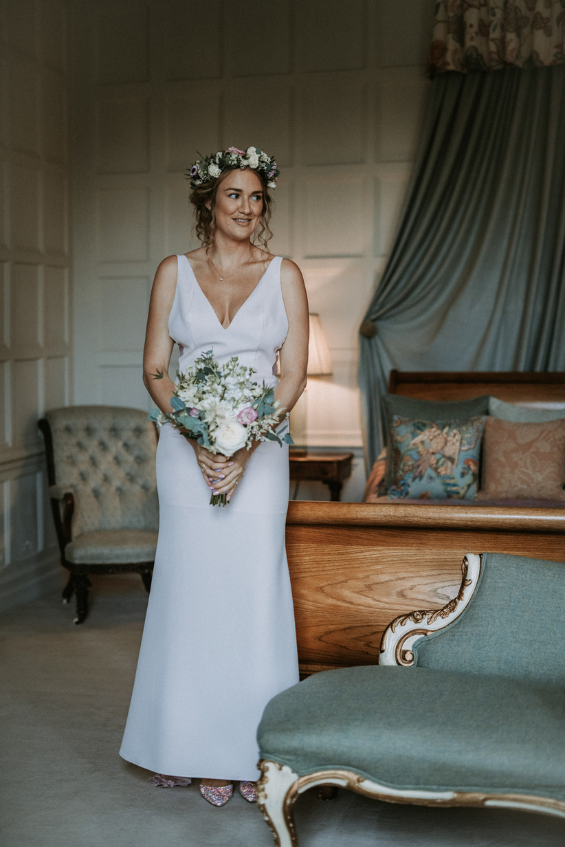 Katherine wearing her wedding dress and floral crown in a bedroom, holding a bouquet