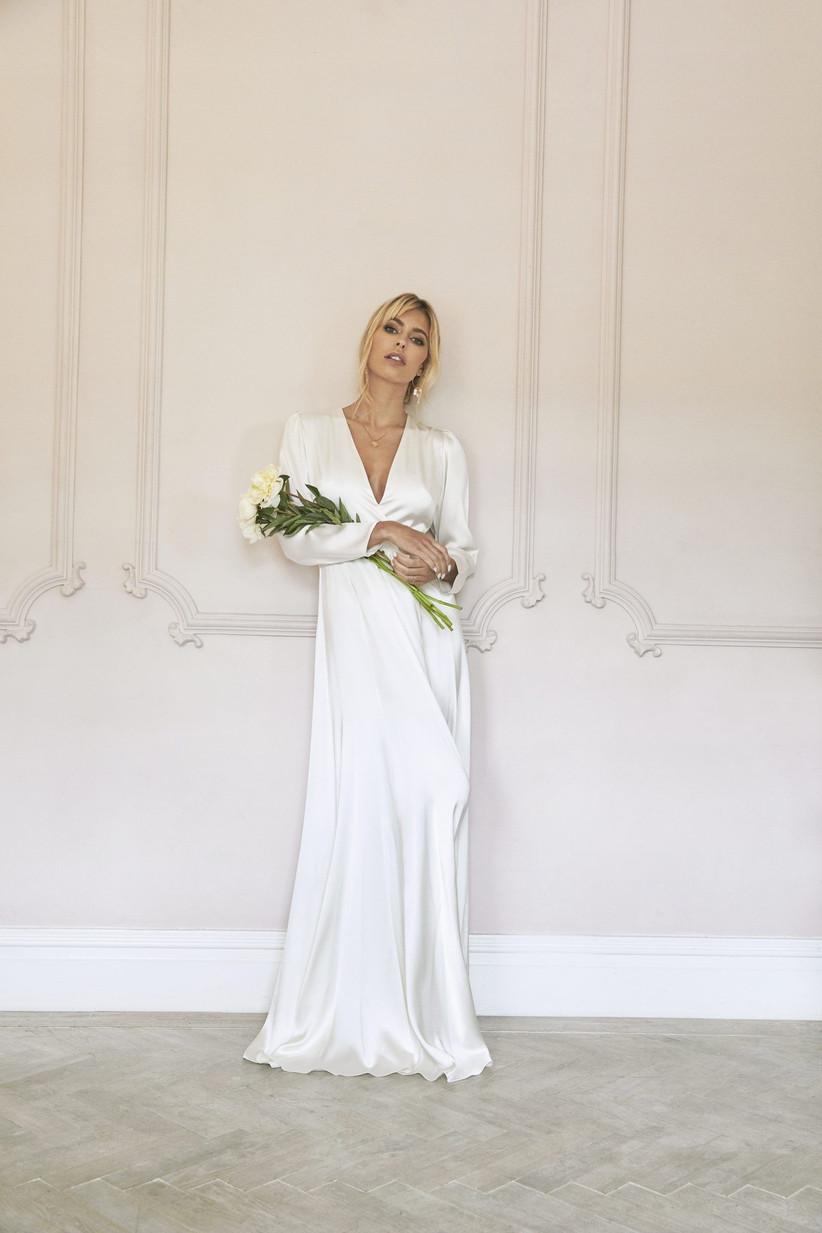 Model wearing a wrap long sleeved wedding dress