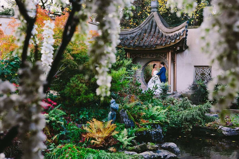 Bride and groom stand under an archway in a garden