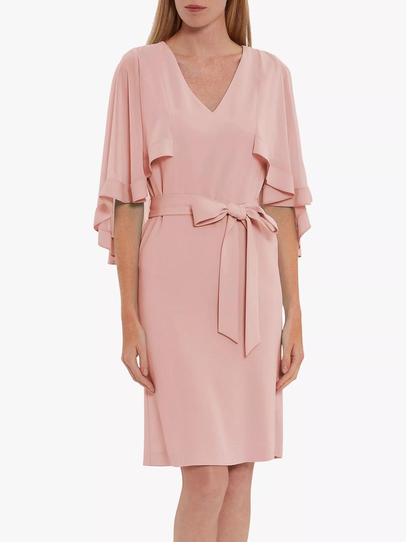 Woman wearing a pale pink caped midi dress