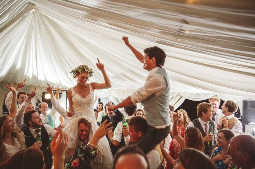 Bride and groom on guest's shoulders dancing